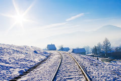 Railroad in snow covered mountains. Under blue sunny sky in wintertime Stock Photography
