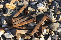 Railroad Spikes. A pile of railroad spikes laying in the rocks alongside a railroad track Stock Image
