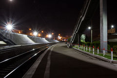 Railroad station. Pedestrian staircase , enclosed lawn , Peron , lights , rails, stretching into the distance Stock Photos