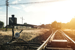 Railroad switch with train in the morning sun.  Royalty Free Stock Images