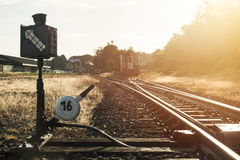 Railroad switch with train in the morning sun.  Stock Images