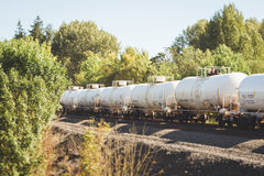 Railroad tank cars rolling through trees Royalty Free Stock Photography