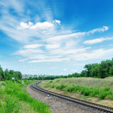 Railroad to green horizon and clouds in blue sky Royalty Free Stock Images
