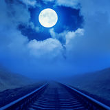 Railroad to horizon in fog and full moon over it Stock Images