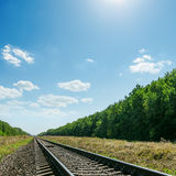 Railroad to horizon in green landscape and blue sky with sun Stock Image