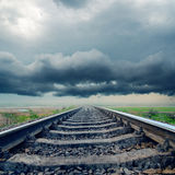 Railroad to horizon in rainy clouds Stock Images