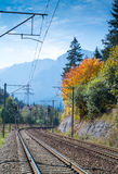 Railroad to the mountains. Double electrified railroad in autumn landscape. Trees with yellow leaves and blue sky. Mountains in far background Stock Photography