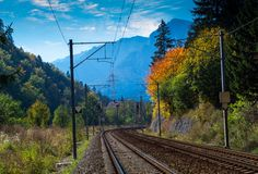 Railroad to the mountains. Double electrified railroad in autumn landscape. Trees with yellow leaves and blue sky. Mountains in far background Royalty Free Stock Photos