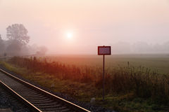 Railroad track during autumn foggy morning Royalty Free Stock Images
