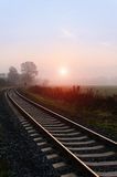 Railroad track during autumn foggy morning Stock Photo