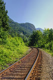 Railroad track in countryside mountain area Royalty Free Stock Photo