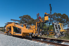 Railroad track machine for tamping and clamping Stock Image