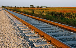 Railroad track near farm land at sunset. stock photos