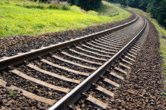 Railroad track perspective into a forest area. Railroad tracks vanishing into a forest area Stock Photos