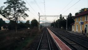 Railroad track from the rear of a high speed train in Eskisehir, Turkey. Gokcekisik, Eskisehir, Turkey - October 09, 2017: Train passing by a village in Tepebasi stock video