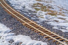 Railroad track on a rocky and snowy ground. Close up of a railroad track curving through a rocky ground. Snow can be seen on the rocky and grassy ground royalty free stock photos