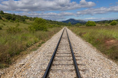 Railroad Track in Straight, in Mountainous Landscape. Straight narrow road in spring landscape with mountains in the background that runs between vegetation Royalty Free Stock Photography