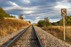 Railroad Track in Straight with Whistle signal in first term. Straight narrow railroad track in field landscape and signal with a whistle S Stock Photography