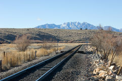 Railroad Tracks. Santa Fe Railroad tracks in rural New mexico turning northward with the Sierra Ladrones mountain in the distance royalty free stock photography