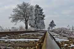 Railroad tracks. Straight railroad tracks vanishing into the winter landscape Stock Photos