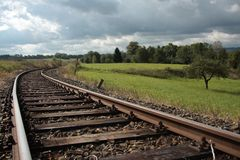 Railroad tracks. Railway lines in the vicinity of the forest, meadow and cloudy sky Stock Images