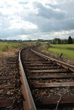 Railroad tracks. Railway lines in the vicinity of the forest, meadow and cloudy sky Stock Photos