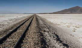 Railroad tracks across Salar de Chiguana in Sud Lipez Altiplano - The Ferrocarril de Antofagasta - Bolivia. South America Royalty Free Stock Photos