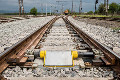 Railroad tracks closeup with derailing block. In foreground Royalty Free Stock Photo