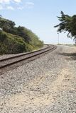 Railroad tracks curving around a bend on a gravel path Stock Photography