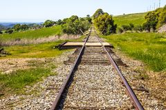 Railroad Tracks Disappearing In Country Hillside. Old Railroad Tracks Disappearing Into Distance Of Sierra Nevada Countryside Hill Royalty Free Stock Images