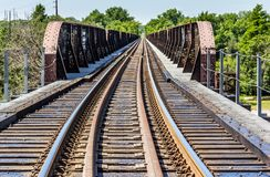 Railroad tracks into the distance and a trestle. Railroad tracks into the distance stock photography