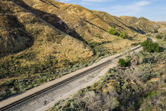 Railroad Tracks in Foothills. Railroad track line along the bottom of desert foothills in California stock image