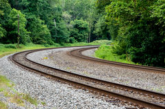 Railroad Tracks in the Forest. Some railroad tracks going around a curve in the forest stock photo