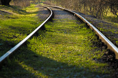 Railroad tracks going around the corner. Curved railroads leading behind the bush Royalty Free Stock Photo