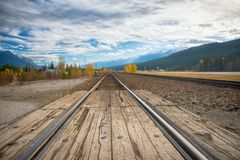 Railroad tracks in the horizon with the Canadian Rocky Mountains. View of railroad tracks in the horizon with the Canadian Rocky Mountains in the background Stock Images