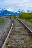 Railroad tracks leading into the Chugach mountains. Railroad tracks leading into the Chugach mountain range stock image