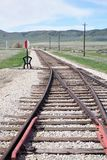Railroad tracks merging at switch. American southwest desert vegetation on hills in background parallel metal iron rails on hand hewn ties and white rock royalty free stock photo