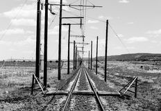 Railroad Tracks in monochrome. Straight railroad tracks in the prairie in the Southwest of the United States in monochrome Stock Photo