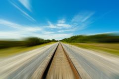 Railroad tracks in motion. Long railroad track reaching the horizon with motion blur stock photography