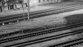 Railroad tracks near the depot under the night sky. Black and white photo. View from above. Stock Photos