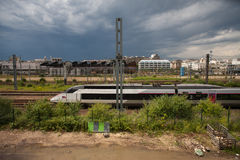 Railroad tracks. North Paris, France. Cityscape of North Paris, with a TGV train on the foreground. Modern buildings on the skyline. Electric pole split the Stock Photos