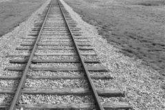 Railroad tracks off center with desert grasses. American southwest scrub brush and tumbleweed in the background surround the black and white parallel metal iron royalty free stock images