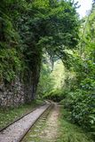 Railroad tracks on the old worn wooden sleepers require urgent repair. The narrow-gauge railway along the ridge. Railway in the mountains Royalty Free Stock Photos