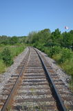 Railroad Tracks in Ontario, Canada. Railroad tracks with the Canadian flag in the background - Spragge, Ontario, Canada Stock Photos