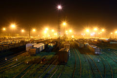 Railroad tracks with railway station & cars a. T night stock photo