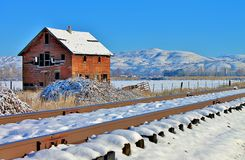 Railroad tracks and red barn. Railroad tracks in the foreground of a snowy red barn Royalty Free Stock Images