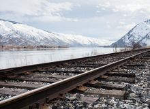 Railroad in Columbia river valley, WA. Railroad tracks running along the snow covered Columbia river valley north of Wenatchee, Eastern Washington state Royalty Free Stock Photo