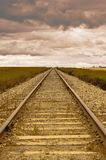Railroad tracks running into a distant cloudy horizon Royalty Free Stock Photo
