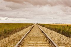Railroad tracks running into a distant cloudy horizon Stock Photography