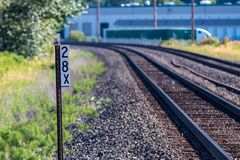 Railroad tracks and sign with building in the distance stock photo